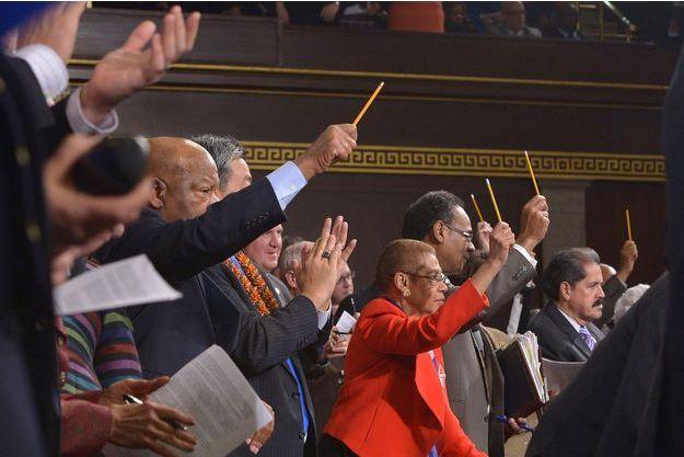 """Les parlementaires américains brandissant leurs crayons pendant le discours d'Obama, en signe de solidarité avec les victimes de l'attentat de """"Charlie Hebdo"""", et en soutien à la liberté d'expression."""