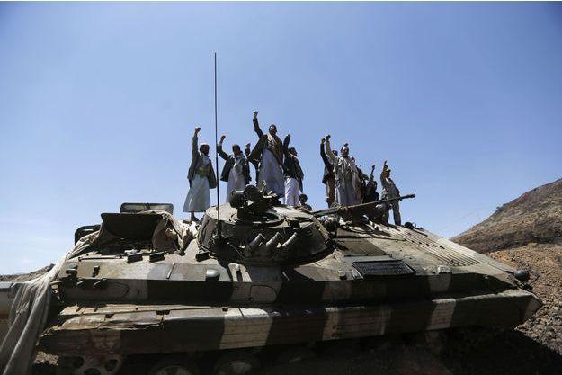 Des Houthis brandissant des armes sur un char de l'armée dont ils ont pris possession.