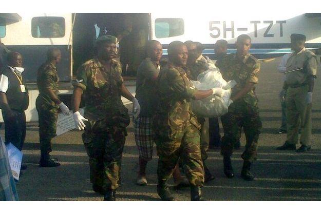 Des militaires portent un corps supposé être celui d'un passager du crash des Comores, à Dar es Salaam.