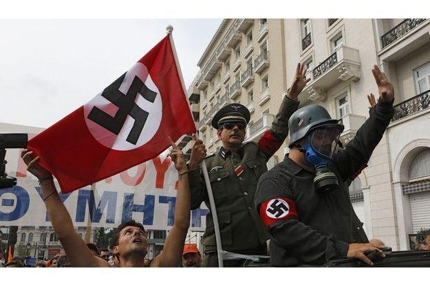 Des manifestants grecs ont défilé mardi à Athènes déguisés en soldats allemands de la Seconde Guerre mondiale et brandissant des drapeaux nazis pour dénoncer la venue de la chancelière allemande Angela Merkel, jugée en partie responsable de l'austérité instaurée dans le pays depuis deux ans