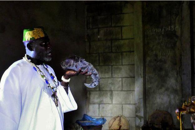 A Djakotomey, dans son temple vaudou, Sa Majesté Dévi Ehoun Zinsou brandit une corne de buffle devant des fétiches durant une cérémonie pour invoquer leur protection.