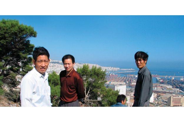 Des expatriés chinois travaillant dans la construction posent devant la baie d'Alger