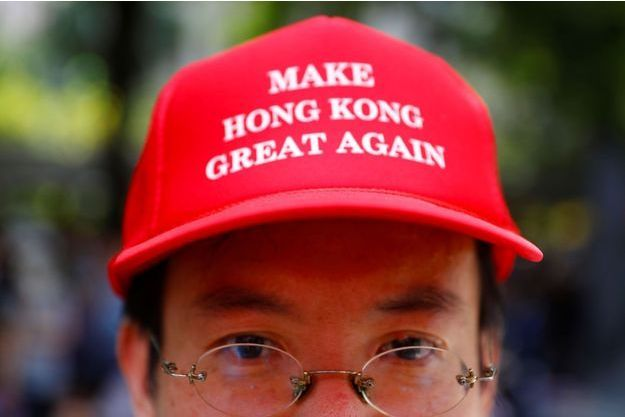 Un homme, à Hong Kong, avec une casquette reprenant le slogan de Donald Trump.