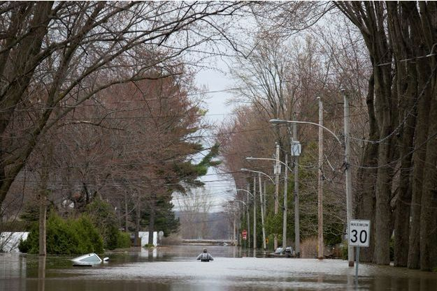 Un résident de Sainte-Marthe-sur-le-Lac, au Québec, traverse une route inondée.