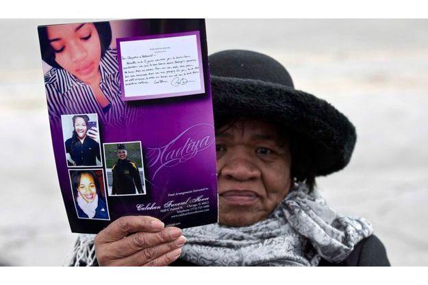 Une femme brandit le programme des funérailles de la jeune Justice pour la jeune Hadiya.