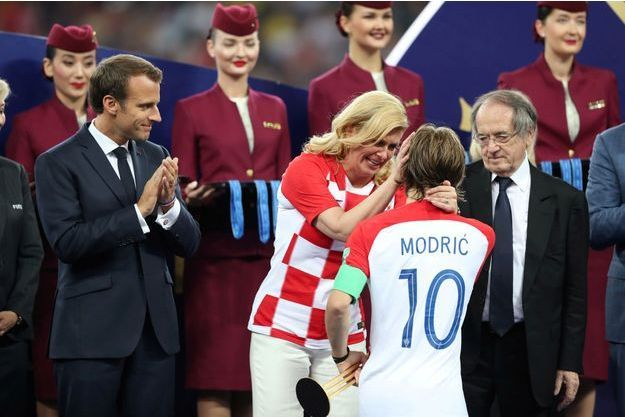 La présidente croate Kolinda Grabar-Kitarović félicite Luka Modric sous les yeux d'Emmanuel Macron.
