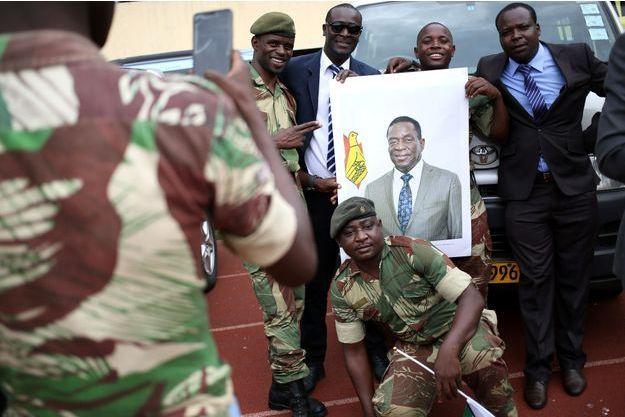 Des militaires zimbabwéens tiennent le portrait du nouveau président Emmerson Mnangagwa, à Harare.