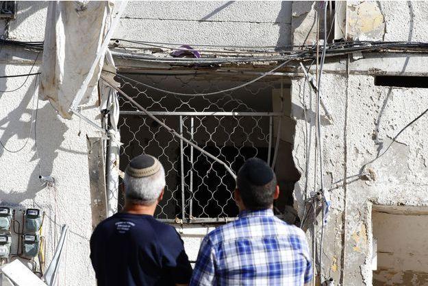 Deux hommes observent un immeuble détruit à Ashkelon, en Israël, le 5 mai 2019.
