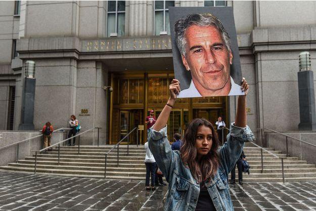 Une manifestante brandit un portrait de Jeffrey Epstein devant un tribunal fédéral à New York lundi.