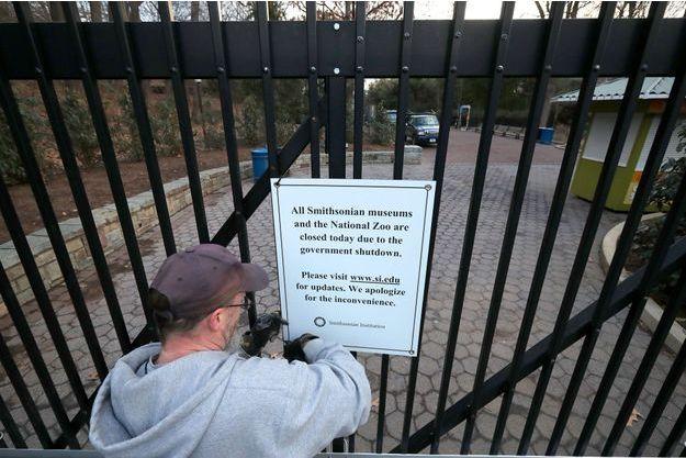 """Lundi, à Washington, un employé du parc zoologique national retire une pancarte annonçant la fermeture du site en raison du """"shutdown""""."""