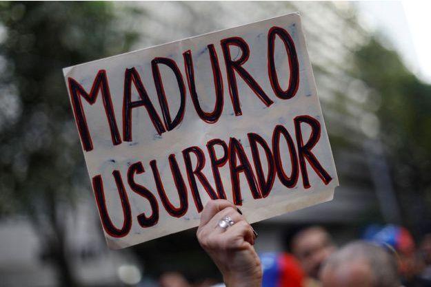Des manifestants brandissent une pancarte anti Maduro au Venezuela.