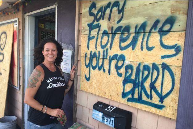 Lisa Lowery devant le Pelican Bar, une institution a Carolina Beach, qui a barricadé ses vitrines «Désolé Florence, tu n'es pas là bienvenue», dit le tag sur la plaque de bois qui protège la vitrine.