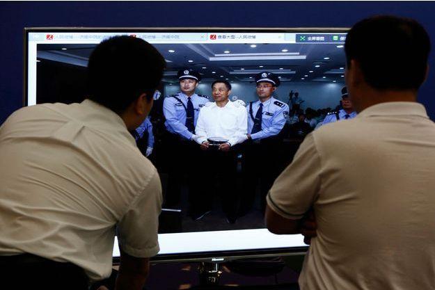 Deux hommes observent la photo transmise par le tribunal de Jinan.