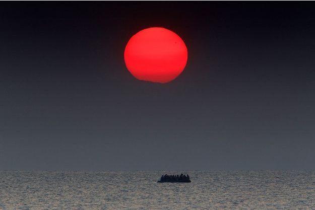 Au lever du soleil, un bateau pneumatique chargé de réfugiés syriens dérive en mer Égée à la suite d'une panne de moteur entre la Turquie et la Grèce pendant sa traversée à destination de l'île grecque de Kos.