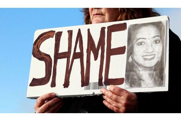 """Une pancarte, sur laquelle il est inscrit """"Honte"""" à côté du visage de Savita, est tenue devant l'hôpital de Galway."""