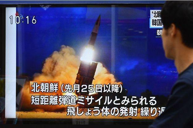 Un passant regarde une télévision à Tokyo, au Japon, vendredi 16 août.