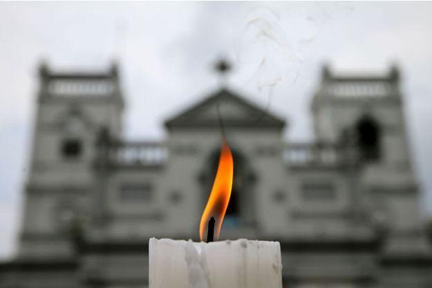 Une bougie brûle devant le sanctuaire Saint-Antoine une semaine après une série d'attentats-suicides commis le dimanche de Pâques à Colombo.
