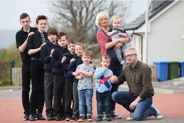 Alexis et David Brett aux côtés de leurs neuf fils. La maman pose enceinte de Rothagaidh, le dernier fils avant la naissance de Cameron.