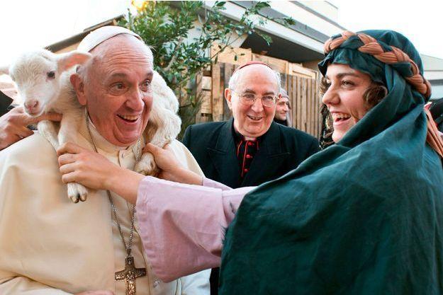 """Le 6 janvier, jour de l'Epiphanie, le Pape, acteur d'une crèche vivante lors de sa visite dans une paroisse de la périphérie romaine. Une """"bergère"""" lui passe un agneau autour du cou sous l'œil amusé du cardinal vicaire de Rome Agostino Vallini."""