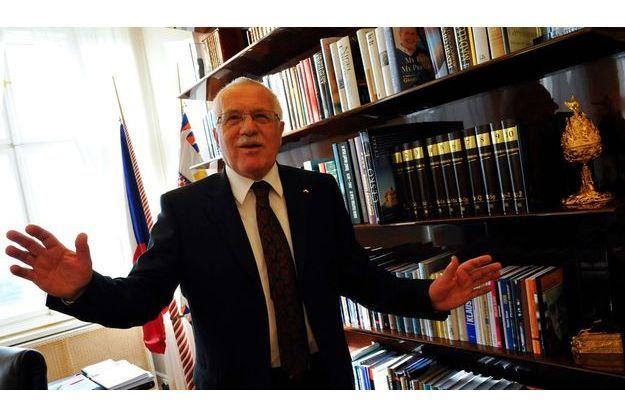 Dans le bureau du président. Vaclav Klaus siège au château présidentiel, à Prague. Derrière lui, on distingue le drapeau national (à g.) et présidentiel (à dr.). Le président tchèque refuse de déployer celui de l'Union européenne.