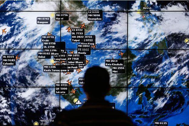 Un homme regarde un écran géant à l'aéroport de Kuala Lumpur pour suivre tous les vols après le décollage