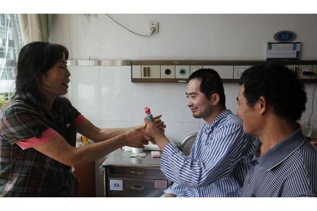 Zhang Tingzhen entouré de ses parents, dans sa chambre d'hôpital.