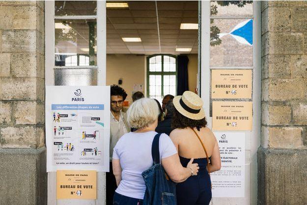 Devant un bureau de vote parisien, dimanche.