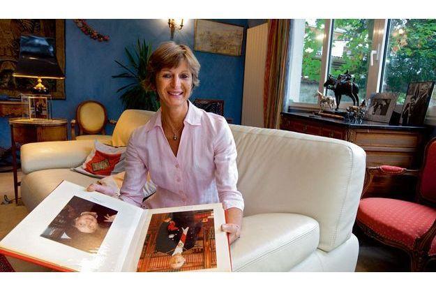 Anne de Larouillère dans sa maison, en région parisienne. Entre ses mains, un album où figurent les photos de ses grands-parents.
