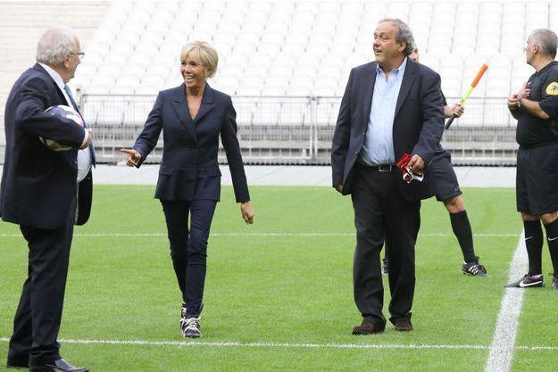 Brigitte Macron, ici avec Jacques Vendroux et Michel Platini, mi-septembre au Stade de France pour le match entre le Variétés Club de France à l'équipe de France des parlementaires.