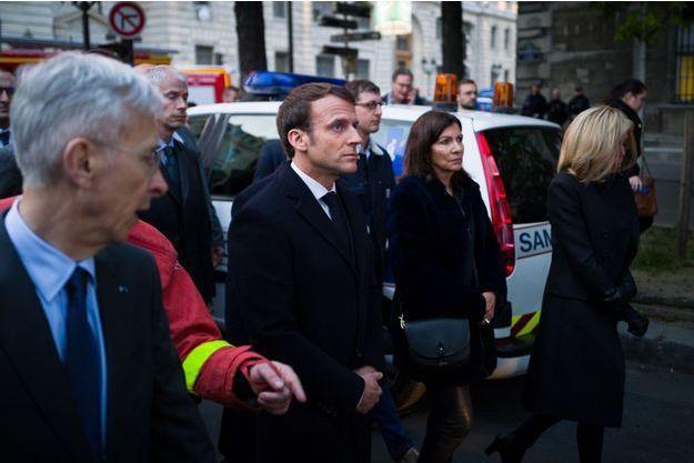Emmanuel Macron, aux côtés d'Anne Hidalgo, Franck Riester et Brigitte Macron, lundi soir près de Notre-Dame de Paris.