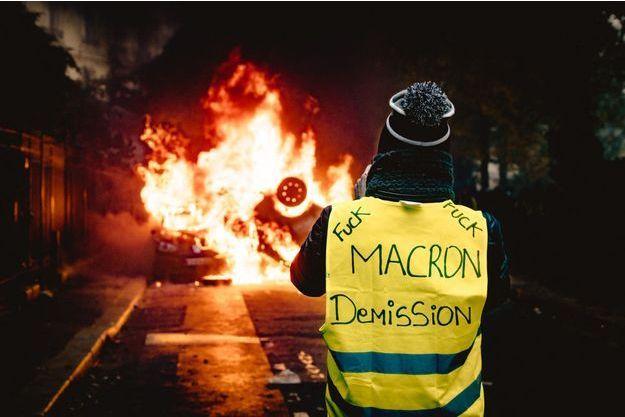 Le premier décembre à Paris, un gilet jaune observe des carcasses de voiture en train de flamber.