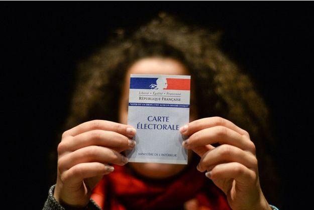 Femme tenant une carte électorale française, le 19 mars 2017.
