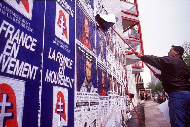 Un colleur d'affiche du RPR recouvre une affiche du PS, en 1991 à Paris.