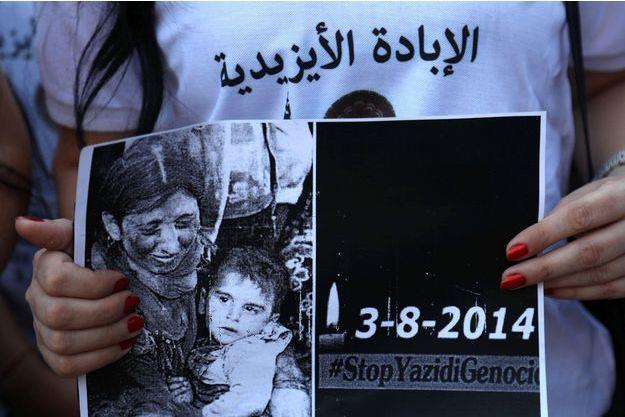 Une femme yézidie tenant une affiche avec le visage de victimes de l'invasion de leur région par Daech en 2014.