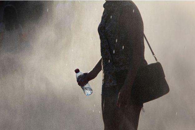 Une femme dans une fontaine avec une bouteille d'eau (image d'illustration).