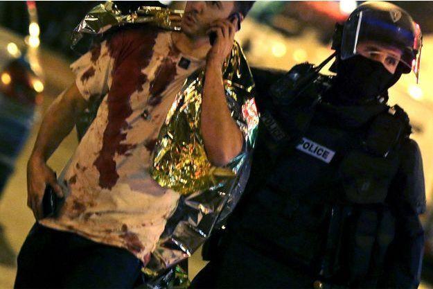 Un homme, le tee-shirt en sang, est accompagné par un policiers aux abords du Bataclan vendredi soir