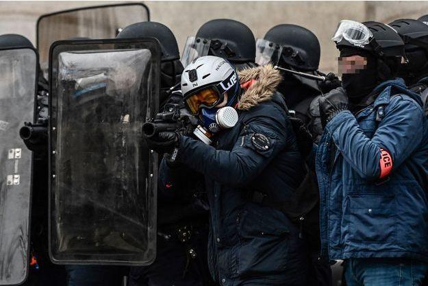 Un policier utilise son lanceur de balles de défense LBD40 à Paris, samedi.