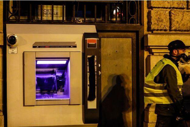 """Un """"gilet jaune"""" devant un distributeur de billets, à Paris (image d'illustration)."""