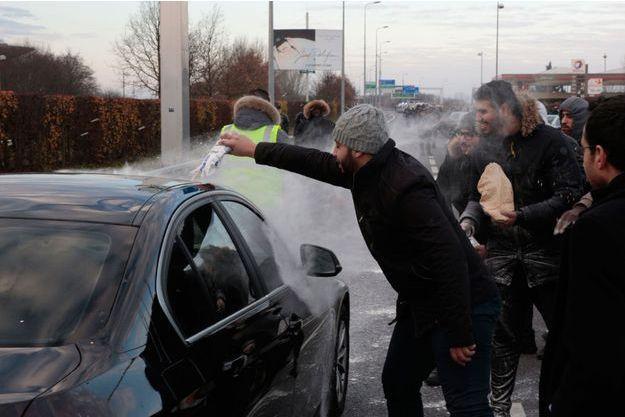 Des conducteurs de VTC jettent du lait sur une voiture lors d'un blocage à l'aéroport de Roissy- Charles de Gaulle, samedi.