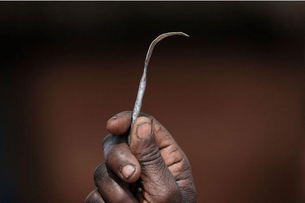 Une femme brandit son outil d'excision, au Ouganda