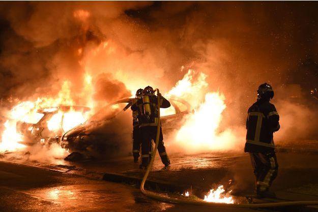 Des pompiers éteignent un véhicule incendié à Nantes dans la nuit de vendredi à samedi.