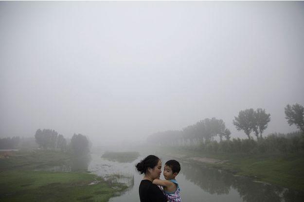 Une mère chinoise tient son enfant dans ses bras tandis qu'un nuage de pollution se dresse derrière eux, dans la province de Hebei.