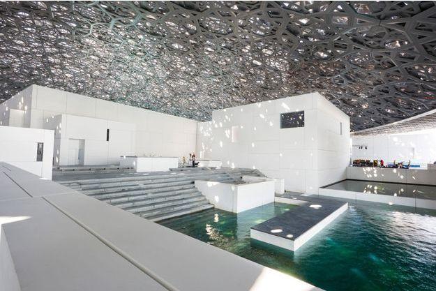 Dans l'entrée du musée, la lumière joue avec les dentelles d'acier et d'aluminium, comme les rayons du soleil à travers les palmes d'une oasis.