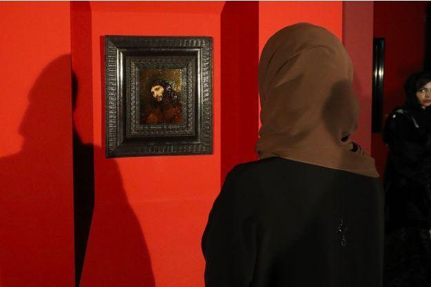 """Une femme contemple la dernière acquisition du Louvre Abu Dhabi, """"Tête de jeune homme, avec les mains jointes: étude de la figure du Christ"""" de Rembrandt."""
