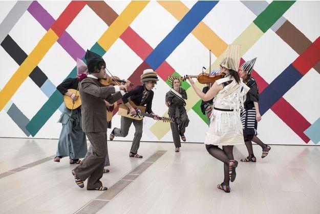 Des musiciens interprètent l'air composé par l'artiste (au centre avec plusieurs chapeaux).