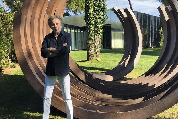 Dans sa propriété du Muy, le Moulin des Serres, l'artiste pose devant une de ses sculptures, l'Arc.