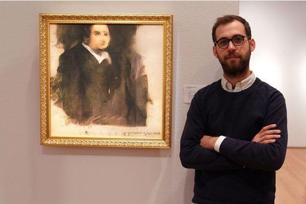 """Pierre Fautrel aux côtés de sa toile """"Portrait d'Edmond de Belamy"""""""