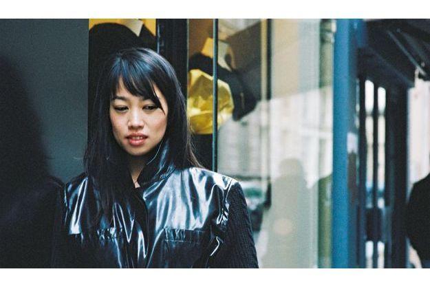 Ce jour-là, chez Neila, sa boutique vintage préférée à Paris, Yi Zhou essaie le trench créé par Yves Saint Laurent pour Catherine Deneuve dans « Belle de jour ».