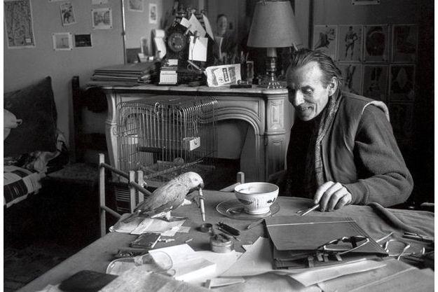 Louis-Ferdinand Céline en 1957 dans sa maison de Meudon. L'écrivain, alors âgé de 63 ans, est assis devant un bol de café posé sur la table sur laquelle se trouve son perroquet Toto avec un stylo dans le bec.