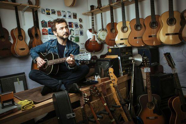 Le chanteur chez son luthier, à Paris.